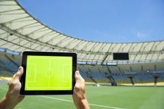 Manos que llevan a cabo el estadio de fútbol Rio Brazil del tablero de las táctica Imagenes de archivo