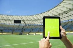 Manos que llevan a cabo el estadio de fútbol Rio Brazil del tablero de las táctica Fotografía de archivo libre de regalías