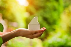 Manos que llevan a cabo el modelo de madera de la casa Compra de un nuevo concepto del seguro del hogar y de la casa imagen de archivo libre de regalías