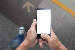 Manos que llevan a cabo el paseo y que usan smartphone Imagen de archivo libre de regalías