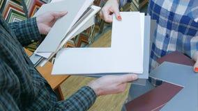 Manos que llevan a cabo el passepartout para la imagen del paquete en marco imágenes de archivo libres de regalías