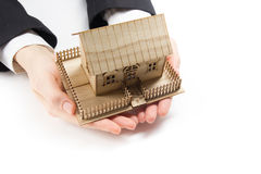 Manos que llevan a cabo el pequeño modelo de la casa Concepto 6 de las propiedades inmobiliarias Foto de archivo