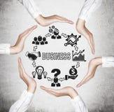 Manos que llevan a cabo iconos del negocio Imagen de archivo libre de regalías