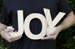 Manos que llevan a cabo la alegría de la palabra Fotos de archivo libres de regalías