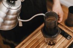 Manos que llevan a cabo la caldera y los aeropress de acero, taza de cristal, escalas, granos de café en la tabla de madera Baris imagen de archivo
