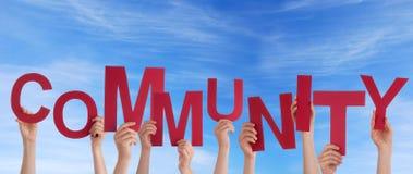 Manos que llevan a cabo a la comunidad en el cielo Imagenes de archivo