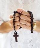 Manos que llevan a cabo la fe cruzada del rezo en la religión del cristianismo fotos de archivo