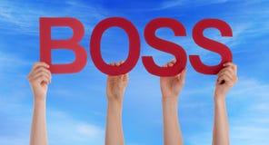 Manos que llevan a cabo la palabra recta roja Boss Blue Sky Foto de archivo