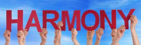 Manos que llevan a cabo la palabra recta roja Harmony Blue Sky Imagen de archivo libre de regalías
