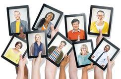 Manos que llevan a cabo los dispositivos de Digitaces con las caras de la gente Imágenes de archivo libres de regalías