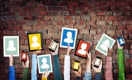 Manos que llevan a cabo los dispositivos de Digitaces con los avatares Imagen de archivo libre de regalías