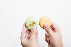 Manos que llevan a cabo macarons Imagen de archivo libre de regalías