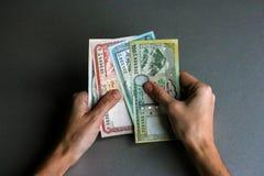 Manos que llevan a cabo moneda nepalesa