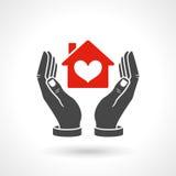 Manos que llevan a cabo símbolo de la casa con forma del corazón Foto de archivo libre de regalías