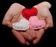 Manos que llevan a cabo tres diversos corazones Fotos de archivo