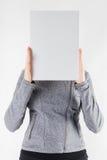 Manos que llevan a cabo un espacio en blanco del Libro Blanco en el fondo blanco Imagen de archivo