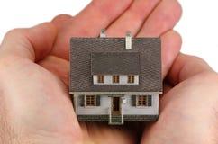 Manos que llevan a cabo un hogar miniatura Fotos de archivo