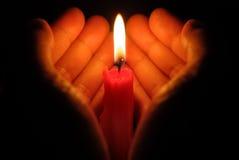 Manos que llevan a cabo una vela ardiente Foto de archivo libre de regalías