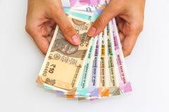 Manos que llevan a cabo 10, 50, 100, 200, 500 y 2000 rupias indias a estrenar de billetes de banco