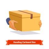 Manos que llevan una entrega de la caja de cartón Imagen de archivo