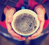 Manos que mantienen calientes, sosteniendo una taza caliente de té o de café Imagen de archivo libre de regalías