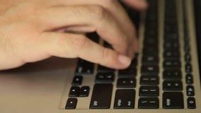 Manos que mecanografían el teclado negro y que golpean la llave de vuelta metrajes