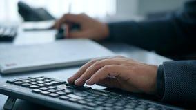 Manos que mecanografían en el teclado de ordenador, hombre que trabaja en la PC en oficina metrajes