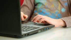 Manos que mecanografían en el teclado del ordenador portátil metrajes
