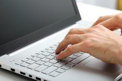 Manos que mecanografían en el teclado del ordenador portátil fotografía de archivo