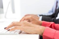 Manos que mecanografían en los teclados de ordenador Foto de archivo libre de regalías