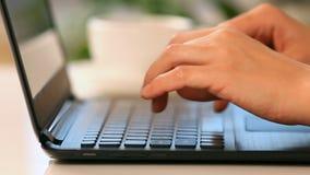 Manos que mecanografían en un teclado del ordenador portátil almacen de metraje de vídeo