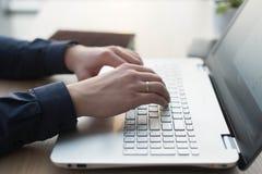 Manos que mecanografían en un teclado del ordenador portátil Un hombre trabaja en una oficina en su lugar de trabajo Foto de archivo libre de regalías