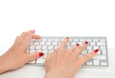 Manos que mecanografían en el teclado de ordenador inalámbrico remoto Foto de archivo libre de regalías