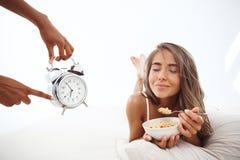 Manos que muestran tiempo en el despertador a la muchacha hermosa que miente en cama fotografía de archivo