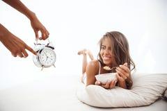 Manos que muestran tiempo en el despertador a la muchacha hermosa que miente en cama imagen de archivo libre de regalías