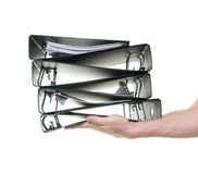 Manos que pasan una pila de carpetas de anillo Imagen de archivo libre de regalías
