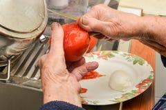 Manos que pelan el tomate Foto de archivo libre de regalías