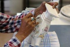Manos que pintan la cerámica de la cerámica de Delft en Holanda Imágenes de archivo libres de regalías