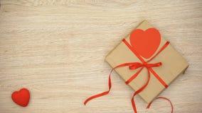 Manos que ponen la caja de regalo hecha a mano en la tabla, celebración de día de San Valentín, romántica almacen de video