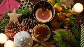 Manos que ponen una taza de té de la Navidad en la tabla adornada con las velas festivas 4K metrajes