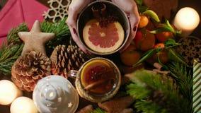 Manos que ponen una taza de té de la Navidad en la tabla adornada con las velas festivas 4K Imagenes de archivo