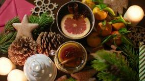 Manos que ponen una taza de té de la Navidad en la tabla adornada con las velas festivas 4K Foto de archivo libre de regalías