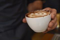 Manos que presentan el café delicioso con la espuma de adornamiento poner crema de la leche en la taza Imagen de archivo libre de regalías