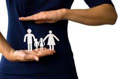 Manos que protegen a una familia de cadena de papel Foto de archivo libre de regalías