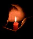 Manos que protegen una luz de una vela Imagen de archivo