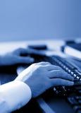 Manos que pulsan en una computadora portátil imagen de archivo