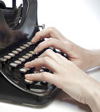 Manos que pulsan en una máquina de escribir del viejo estilo. Imagenes de archivo