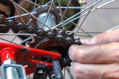 Manos que quitan la rueda de bicicleta Imágenes de archivo libres de regalías