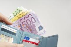 Manos que quitan notas euro de la cartera Imagen de archivo libre de regalías