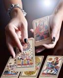 Manos que realizan la lectura de la carta de tarot Imagenes de archivo